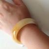 HB07J กำไลหยกพม่าแท้ หยกน้ำผึ้งสีคาลาเมลเหลืองอ่อนแกมส้ม 5.8 cm.